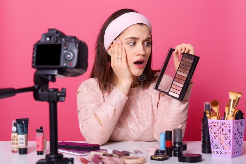 La mujer joven encantadora se sienta delante de cámara, ha sorprendido la expresión, rodeada con los productos de belleza La much fotos de archivo libres de regalías