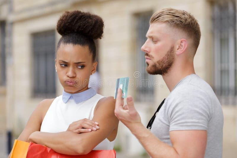 La mujer joven enfadada como hombre sostiene la tarjeta de crédito mientras que hace compras imágenes de archivo libres de regalías