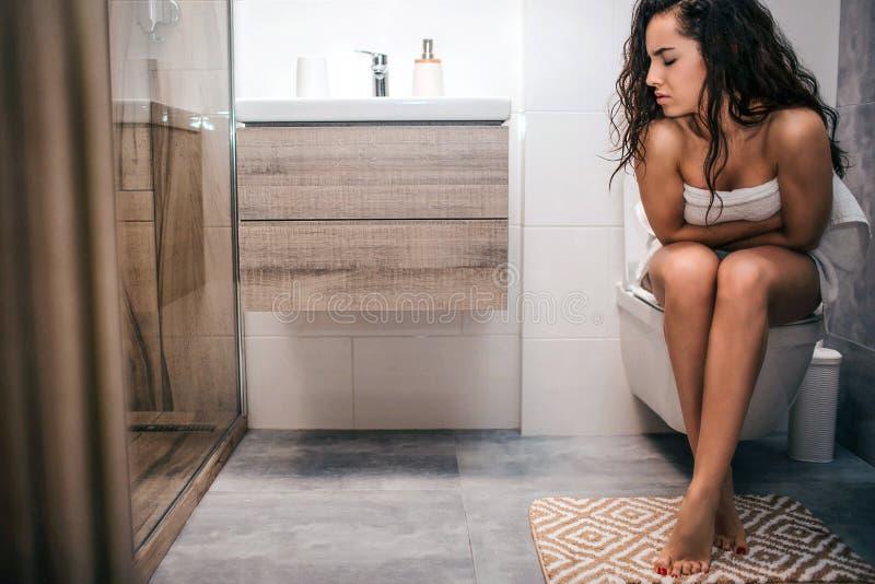 La mujer joven enferma del pelo negro se sienta en tiolet en lavabo Ella tiene problemas del estómago Solamente Dolor y dolor imagen de archivo libre de regalías