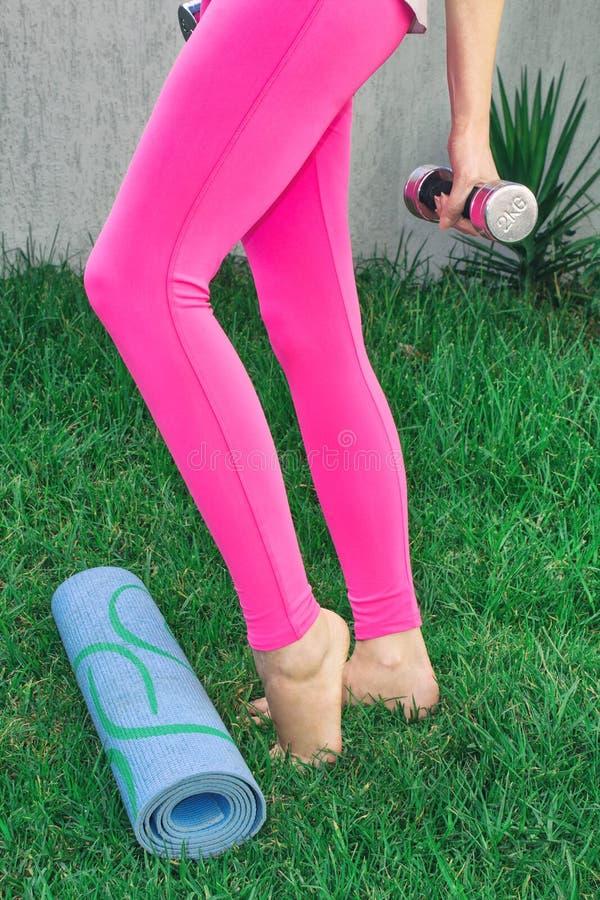 La mujer joven entra para los deportes Piernas femeninas que juegan deportes en naturaleza con pesas de gimnasia foto de archivo