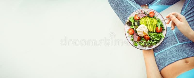 La mujer joven es de reclinaci?n y de consumici?n de una comida sana despu?s de un entrenamiento imagen de archivo libre de regalías