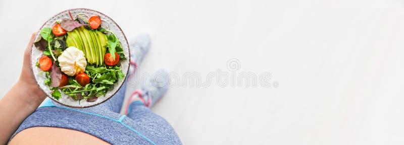 La mujer joven es de reclinaci?n y de consumici?n de una comida sana despu?s de un entrenamiento fotos de archivo libres de regalías