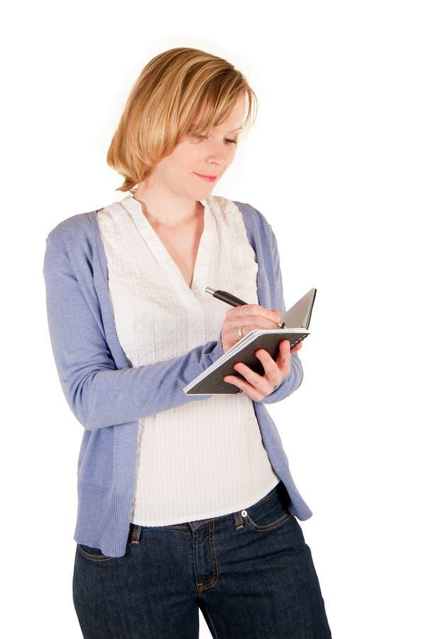 La mujer joven escribe en un cuaderno fotografía de archivo