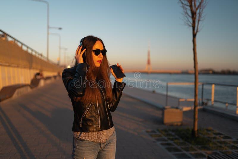 La mujer joven escucha la música en auriculares cerrados a través de su teléfono que lleva una chaqueta de cuero y vaqueros en imagenes de archivo