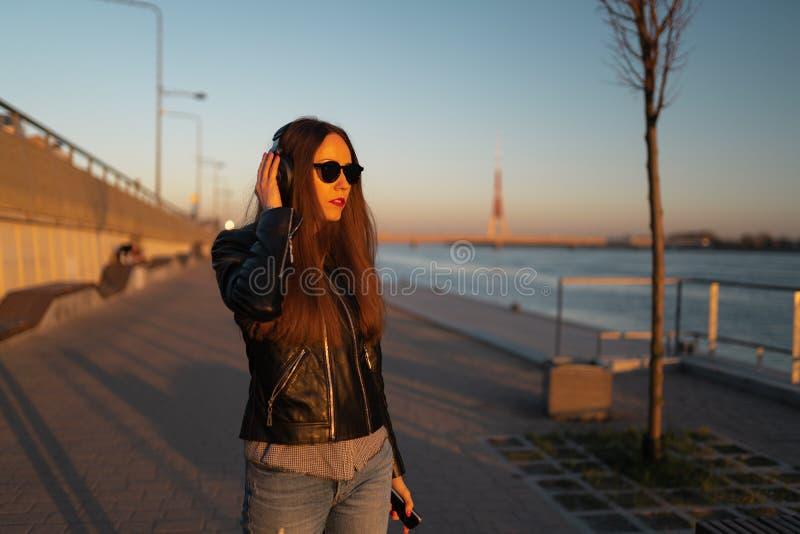 La mujer joven escucha la música en auriculares cerrados a través de su teléfono que lleva una chaqueta de cuero y vaqueros en fotos de archivo libres de regalías