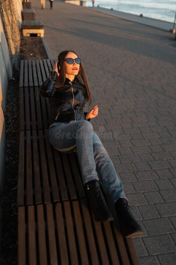 La mujer joven escucha la música en auriculares cerrados a través de su teléfono que lleva una chaqueta de cuero y vaqueros en imagen de archivo libre de regalías