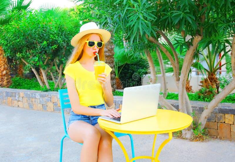 La mujer joven está bebiendo el jugo usando el ordenador portátil se sienta en un café imagenes de archivo