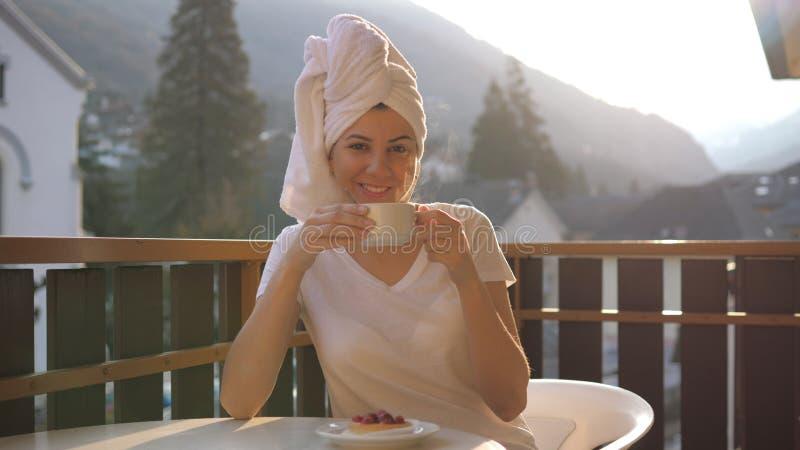 La mujer joven está bebiendo una taza de té o de café en los rayos del sol en las montañas fotografía de archivo