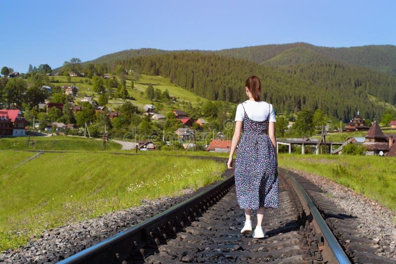 La mujer joven está caminando a lo largo de las pistas ferroviarias Montañas verdes fotografía de archivo libre de regalías