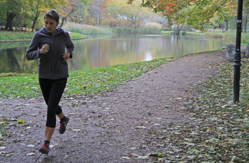 La mujer joven está corriendo en el parque de Varsovia imagen de archivo