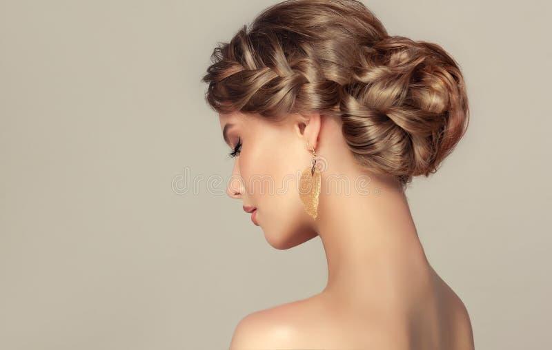 La mujer joven está demostrando el pelo rubio profundo recolectado en peinado elegante foto de archivo libre de regalías