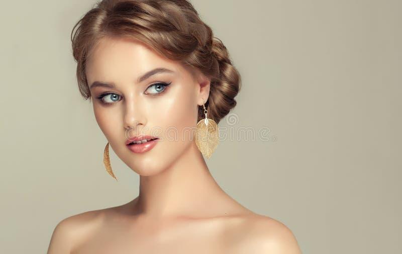 La mujer joven está demostrando el pelo rubio profundo recolectado en peinado elegante imagen de archivo