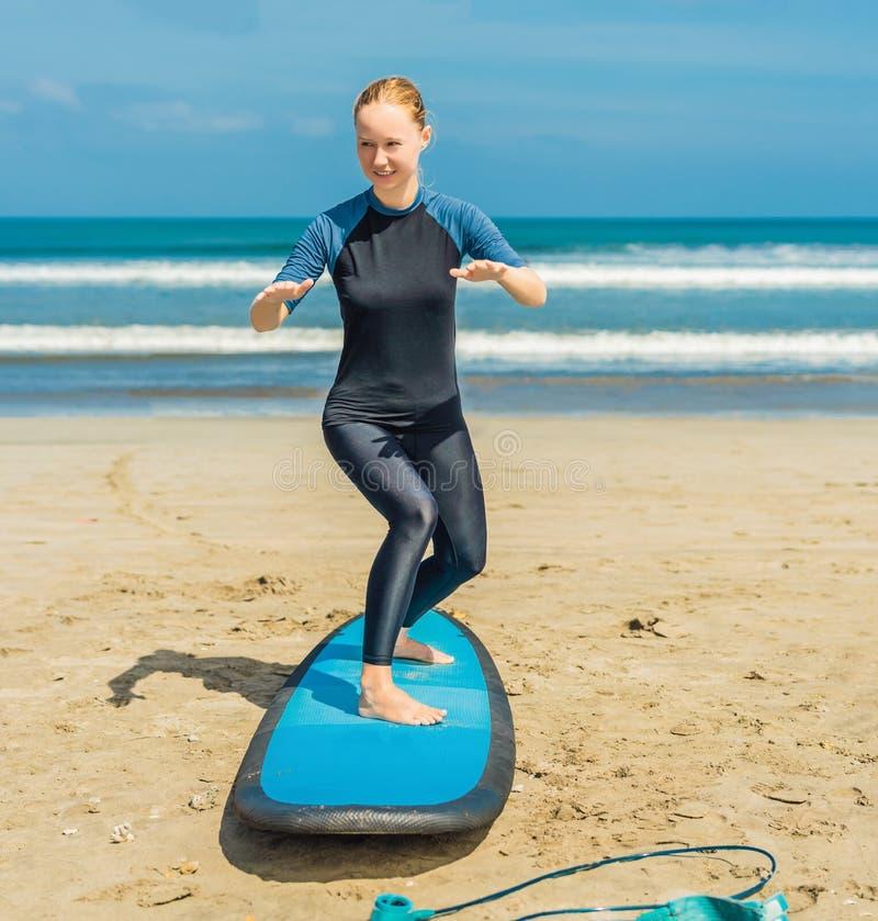 La mujer joven está entrenando para colocarse en la resaca antes de la primera lección que practica surf fotografía de archivo