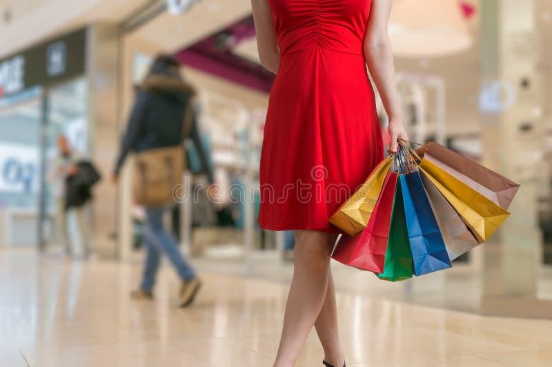 La mujer joven está haciendo compras en alameda y sostiene muchos bolsos coloridos imagenes de archivo