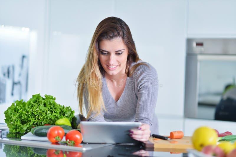 La mujer joven está haciendo compras en línea por la tableta El ama de casa encontró la nueva receta para cocinar en una cocina fotografía de archivo