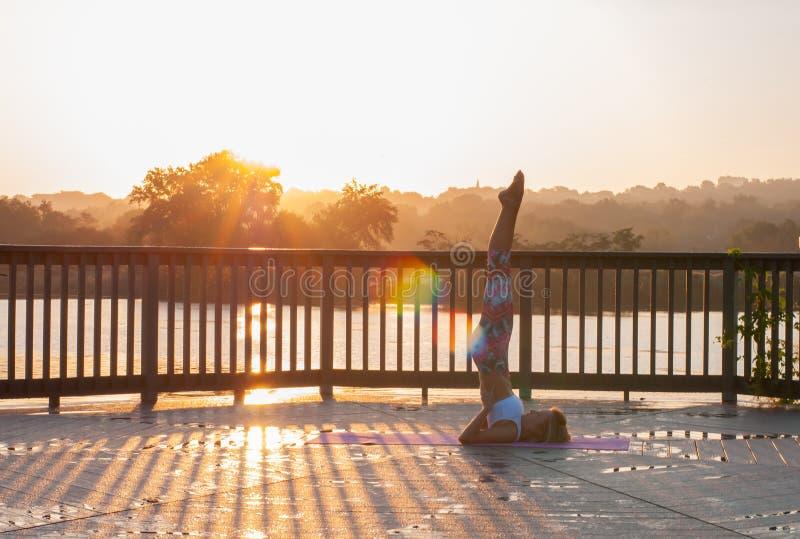 La mujer joven está haciendo yoga en la salida del sol imagen de archivo libre de regalías