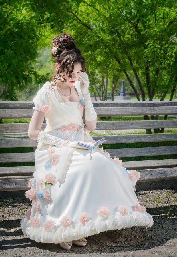 La mujer joven está leyendo un libro que se sienta en un banco imagenes de archivo