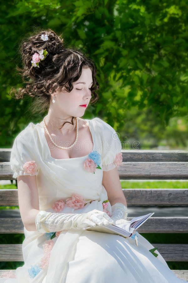 La mujer joven está leyendo un libro que se sienta en un banco fotografía de archivo