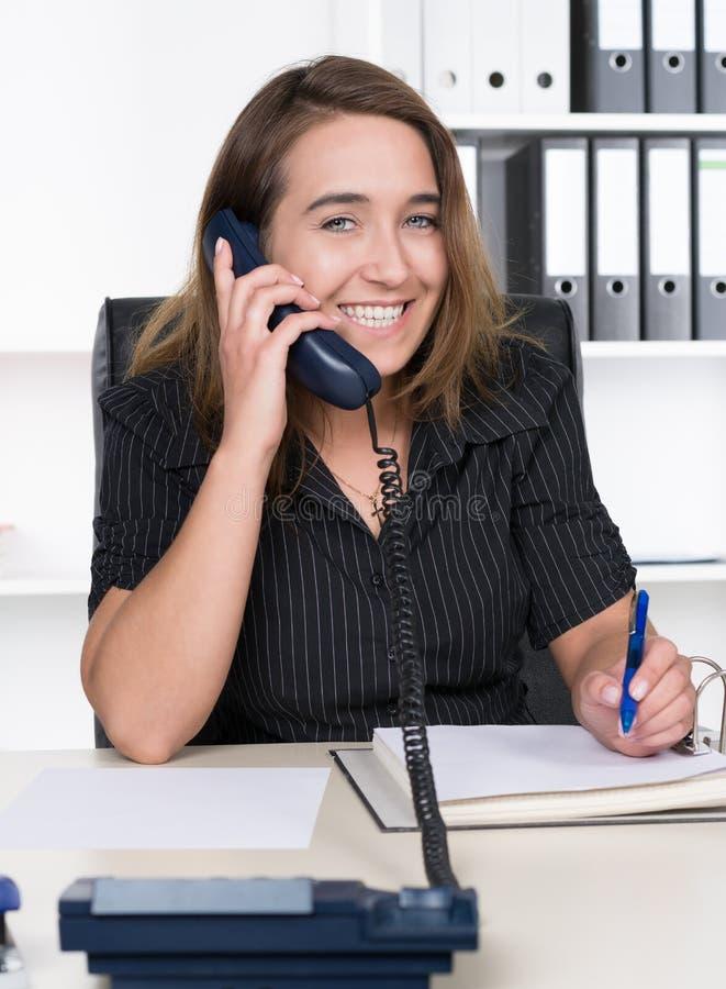 La mujer joven est llamando por tel fono en la oficina for Telefono de la oficina