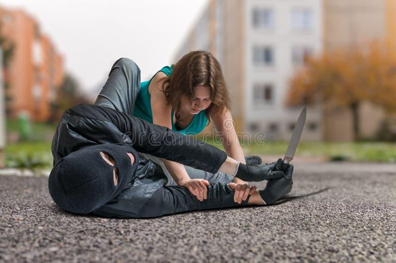 La mujer joven está luchando con el ladrón armado con el cuchillo Concepto de la autodefensa fotos de archivo libres de regalías