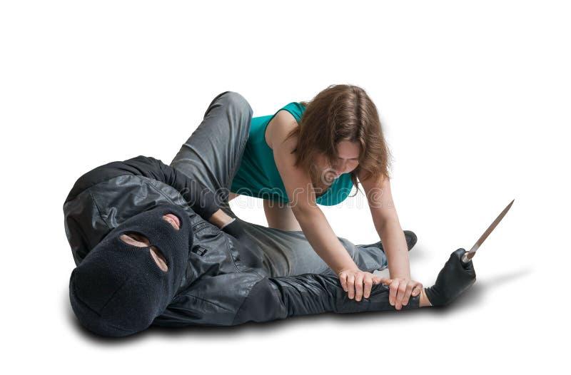 La mujer joven está luchando con el ladrón en la calle Concepto de la autodefensa foto de archivo