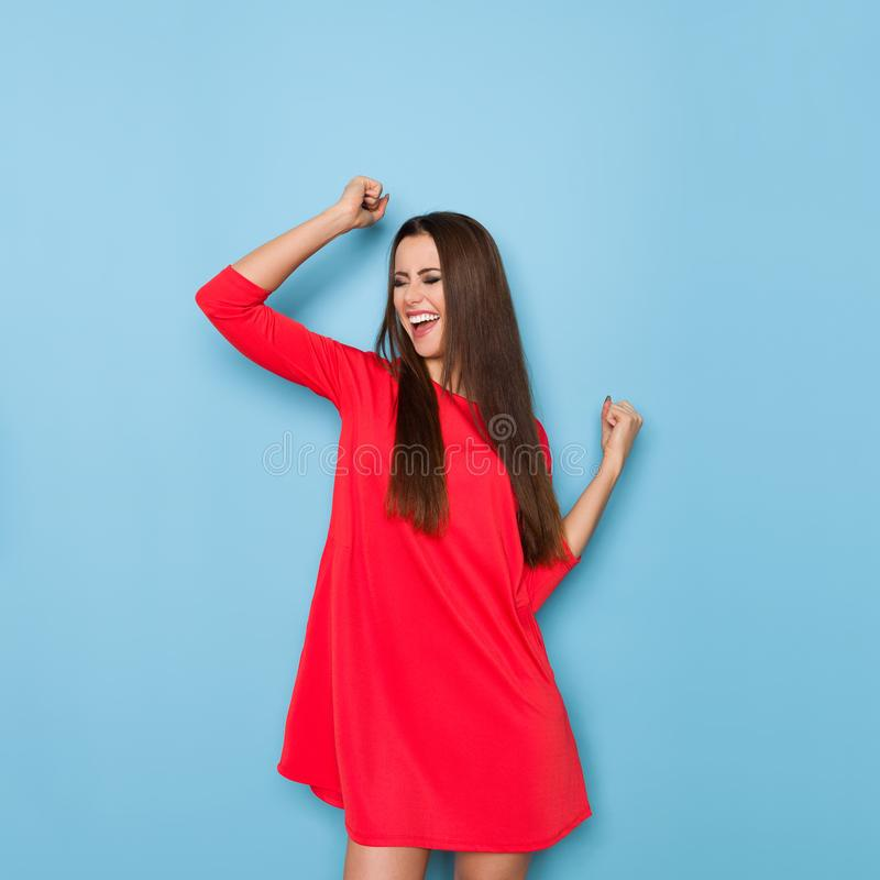 La mujer joven está riendo con los brazos aumentados foto de archivo
