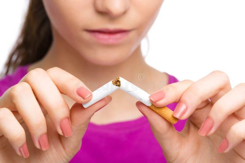 La mujer joven está rompiendo un cigarrillo fotos de archivo