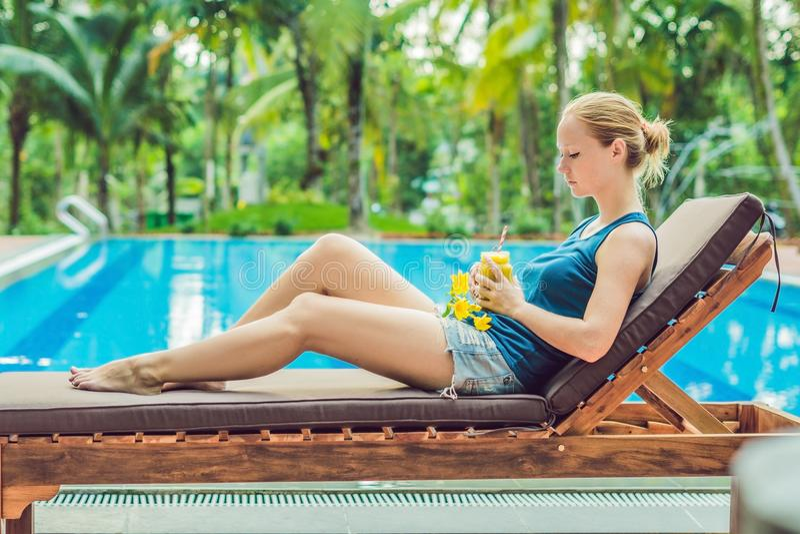 La mujer joven está sosteniendo un smoothie del mango en el fondo de la piscina Smoothie de la fruta - concepto sano de la consum foto de archivo