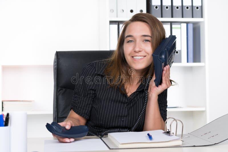 La mujer joven está sosteniendo un teléfono en su oído fotografía de archivo