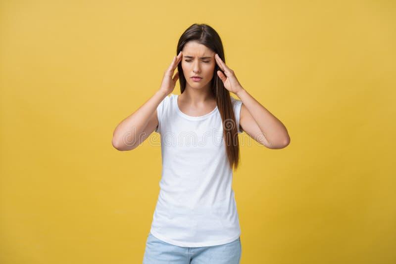 La mujer joven está sufriendo de un dolor de cabeza contra un fondo amarillo Tiro del estudio imagen de archivo