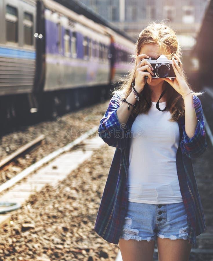 La mujer joven está tomando la foto con la cámara de la película imagen de archivo libre de regalías