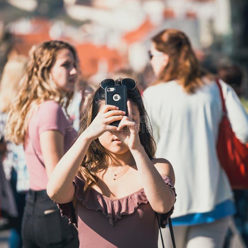 La mujer joven está tomando las fotos con su smartphone en Charles Bridge durante el au hermoso foto de archivo