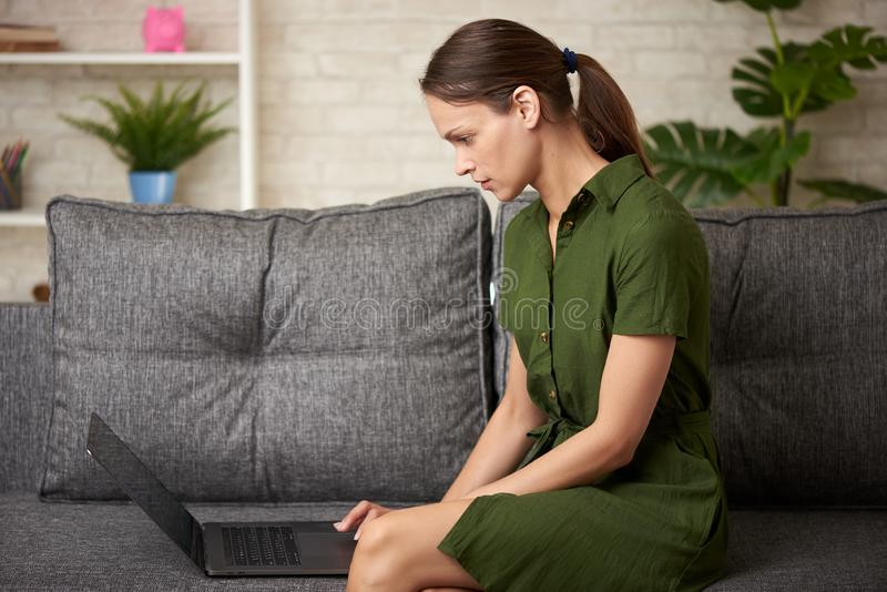 La mujer joven está trabajando con el ordenador portátil que se sienta en un sofá fotos de archivo