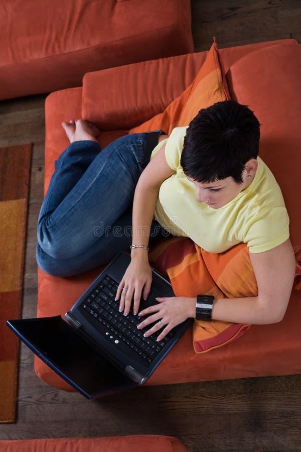La mujer joven está utilizando una computadora portátil imágenes de archivo libres de regalías