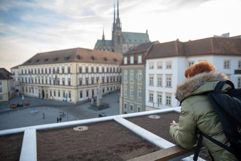 La mujer joven est? mirando Brno de una terraza de visi?n Tome las im?genes de la ciudad en el tel?fono y comp?rtalas en el socia fotos de archivo