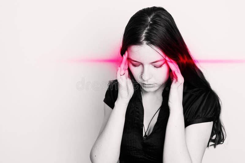 La mujer joven est? sufriendo de un dolor de cabeza Retrato de una muchacha con los puntos del dolor en su cabeza fotos de archivo libres de regalías
