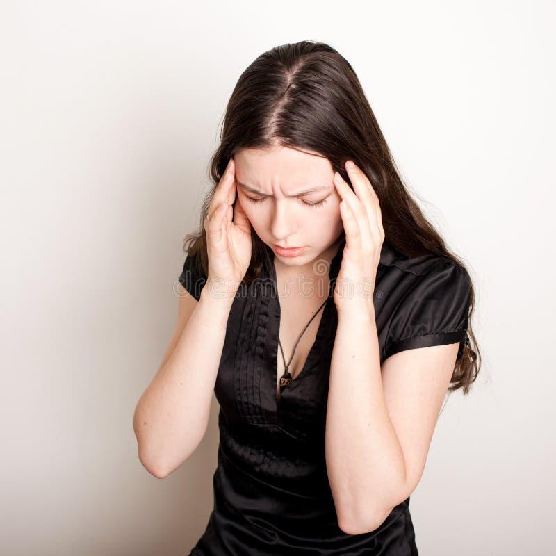 La mujer joven est? sufriendo de un dolor de cabeza Retrato de una muchacha que agarra su cabeza Jaquecas y problemas de la presi foto de archivo