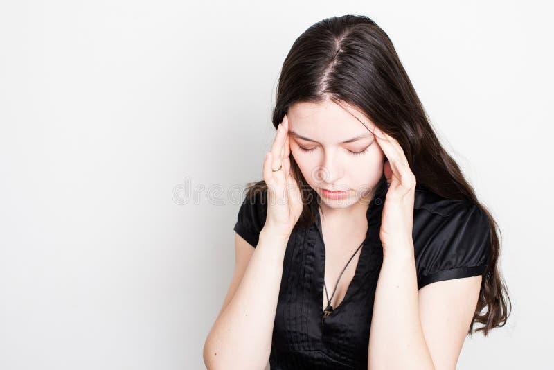 La mujer joven est? sufriendo de un dolor de cabeza Retrato de una muchacha que agarra su cabeza Jaquecas y problemas de la presi imagen de archivo