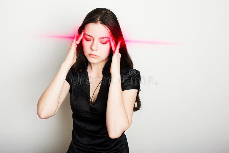 La mujer joven est? sufriendo de un dolor de cabeza Retrato de una muchacha que agarra su cabeza Jaquecas y problemas de la presi foto de archivo libre de regalías