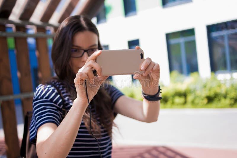 La mujer joven, estudiante, una morenita con los vidrios, se sienta en un banco de parque, toma una foto, mira alrededor fotografía de archivo libre de regalías