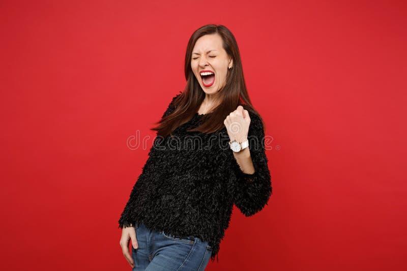 La mujer joven extática en el suéter negro de la piel que hacía gesto del ganador, guardando ojos se cerró, griterío aislado en r imagen de archivo libre de regalías