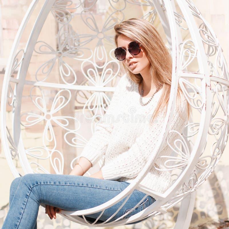 La mujer joven feliz atractiva del inconformista en tejanos en un suéter hecho punto en gafas de sol se está sentando en una sill foto de archivo