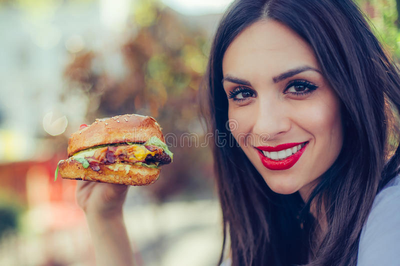 La mujer joven feliz come la hamburguesa sabrosa de los alimentos de preparación rápida fotografía de archivo libre de regalías