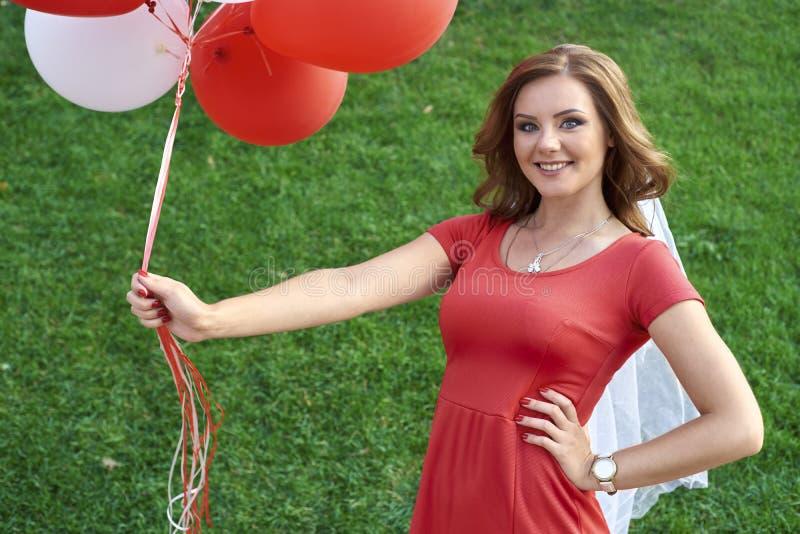 La mujer joven feliz con el látex colorido hincha, al aire libre imagenes de archivo