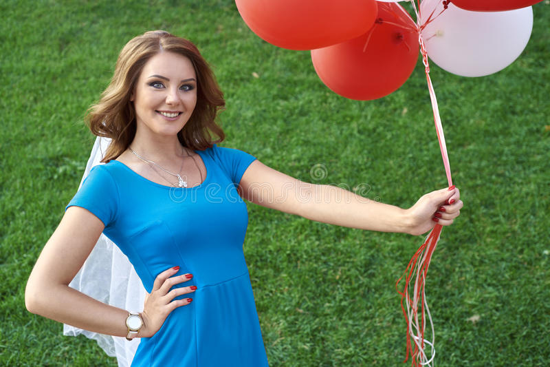 La mujer joven feliz con el látex colorido hincha, al aire libre imagen de archivo