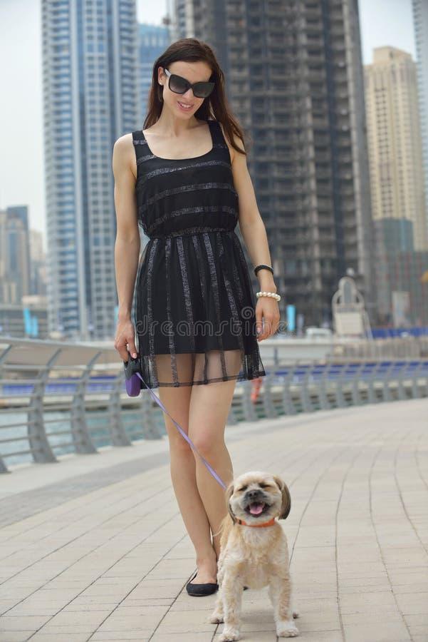 La mujer joven feliz con el perrito se divierte imagen de archivo libre de regalías
