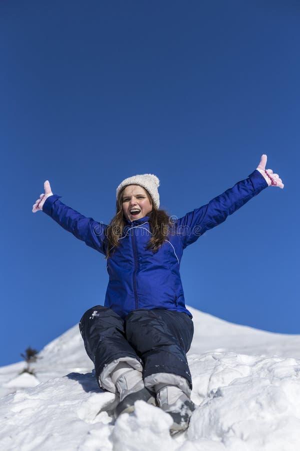 La mujer joven feliz con los brazos aumentó en el top de una montaña imagen de archivo