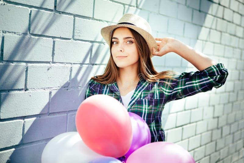 La mujer joven feliz con los globos coloridos sonríe en verano foto de archivo libre de regalías
