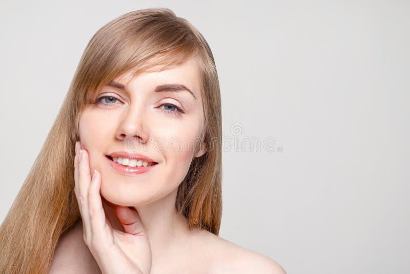 La mujer joven feliz con maquillaje toca su mejilla imágenes de archivo libres de regalías