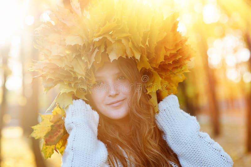 La mujer joven feliz con una guirnalda del amarillo deja caminar en el parque fotos de archivo
